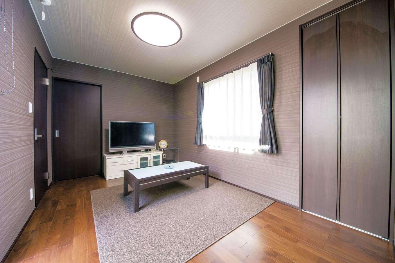 朝日夢工房【子育て、趣味、間取り】1階の一室はご主人の部屋に。漆喰のリビングとは対照的に、落ち着いた色調のクロスとフローリングでくつろぎの空間に