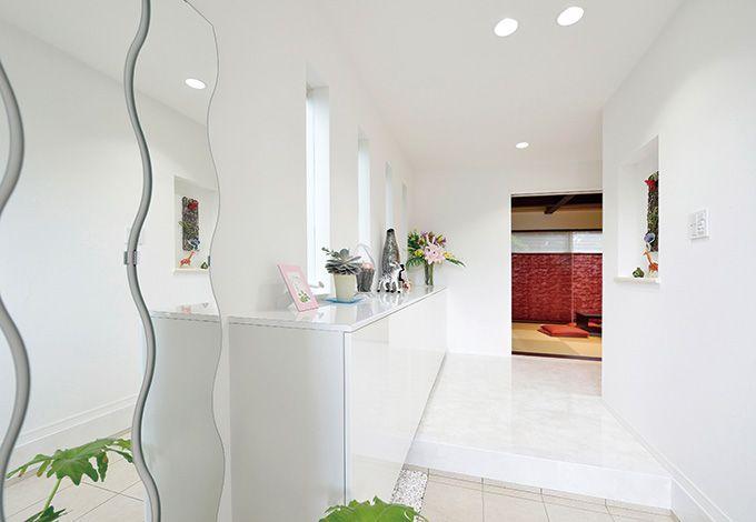 朝日夢工房【デザイン住宅、省エネ、夫婦で暮らす】洗練と清潔感が漂う玄関。和室へ、さらにその先の庭 へという視線の伸びも計算