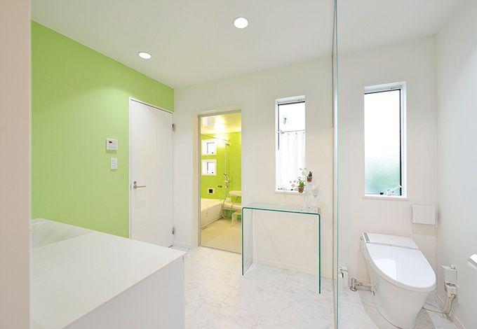 朝日夢工房【デザイン住宅、省エネ、夫婦で暮らす】奥さまが気に入った浴室のグリー ンを、サニタリーのポイントカラー に。先々を考え、寝室から直接利 用できる間取りとした。回遊性も 生まれ、家事効率もアップ