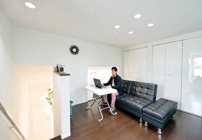 朝日夢工房【デザイン住宅、省エネ、夫婦で暮らす】3 階の書斎スペース。吹き抜けに設置されたガラスからは明るさと2階の様子が運ばれる。ご主人の視線の先に用意されたバルコニーが空間に広がりをも たらす