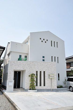 朝日夢工房【デザイン住宅、省エネ、夫婦で暮らす】白い塗り壁と斜めに立てたタイル貼りの壁が住まい手の個性を伝える。通り側はあえて閉じ、外部からの視線を限定している