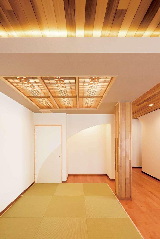 朝日夢工房|畳コーナーは天井を下げ、落ち着きを演出。光天井には、かつて使われていた職人の手による欄間を再利用した。扉の向こうには仏壇が置かれている