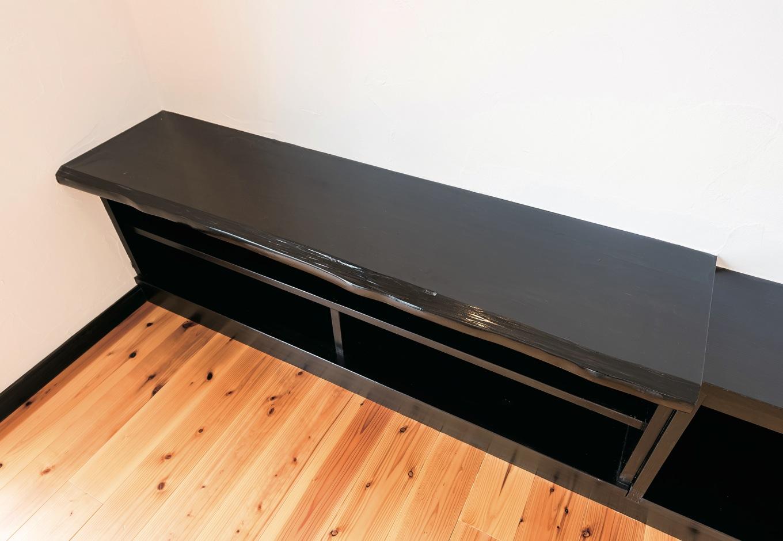 テレビボードは造作で。黒く塗装した一枚板が存在感を示す。白い塗り壁とのモノトーンもシックな印象