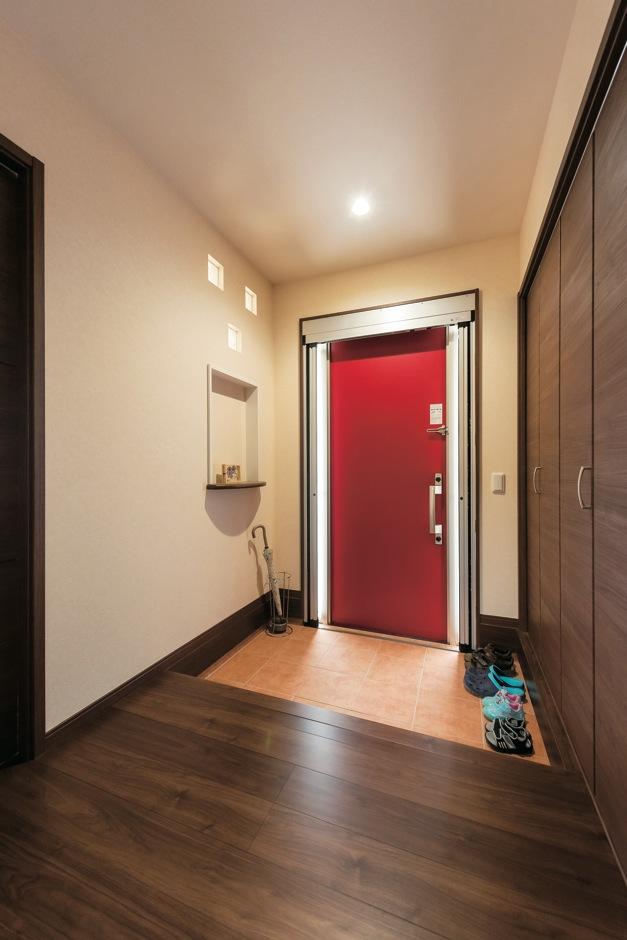 断熱、電気錠の最新式玄関ドア。家全体がシンプルな分、ビビッドな赤がアクセントになっている。玄関ホールにはリビング側のガラスブロックから光が差し込む