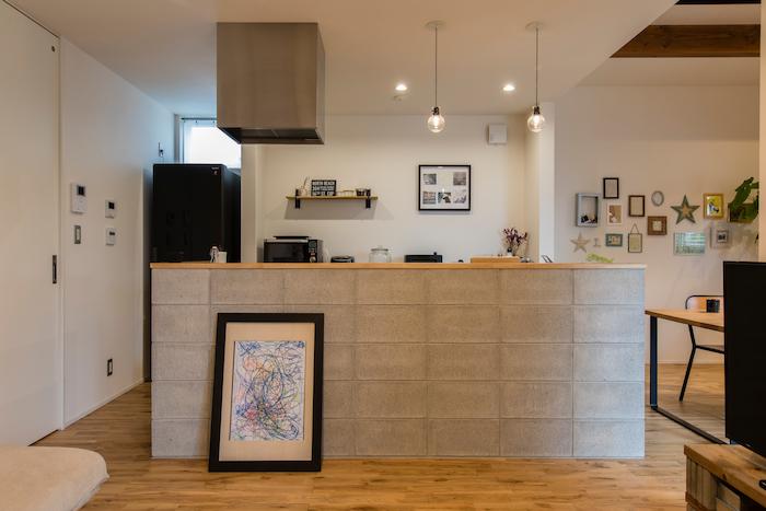 R+house静岡葵・静岡駿河(住宅工房コイズミ)【デザイン住宅、狭小住宅、間取り】「異質な素材を入れたい」と、コンクリートブロックを積んだキッチンの腰壁。ダイニングは少し天井を高くし、梁を見せている