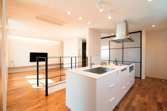 R+house静岡葵・静岡駿河(住宅工房コイズミ)【デザイン住宅、間取り、建築家】2階は、階段を挟んでリビングとDKに分かれる。大きな扉で、キッチン周りの細々としたものはすべて隠す収納に。外壁材を用いた壁はお手入れも簡単
