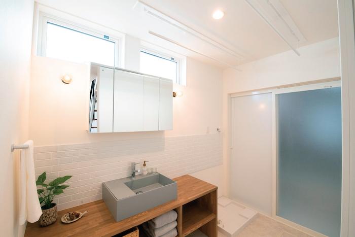 R+house静岡葵・静岡駿河(住宅工房コイズミ)【デザイン住宅、間取り、建築家】1階にある洗面室も、白、グレー、木調のテーマカラーでセンスよくまとめている