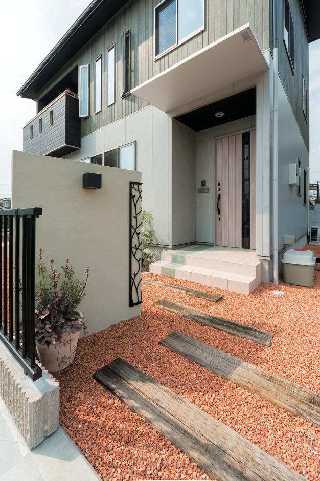 枕木を使ったアプローチが、外観とマッチ。玄関ポーチにライン状に施した緑のタイルがアクセント