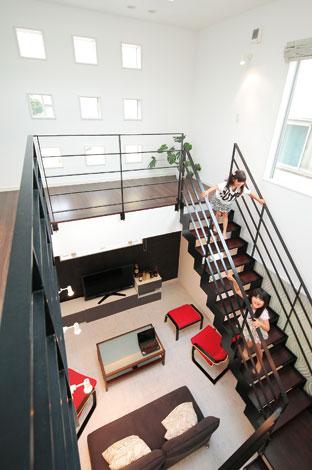 ホームアシスト【デザイン住宅、子育て、間取り】ギャラリーを思わせる吹き抜けの大空間。プラズマカットの黒い階段が白い空間に美しく浮かび上がる
