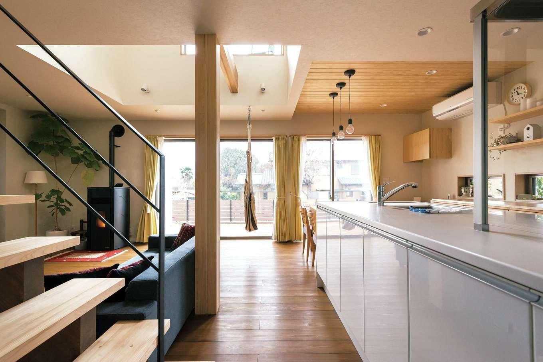 フジモクの家(富士木材)【デザイン住宅、自然素材、インテリア】キッチン下は収納に。壁側にはカウンターを造作し、たっぷりの作業スペースを確保。既存の食器棚やラックに色目をあわせた板を渡すことで、全体の統一感を創出した。見せる収納と隠す収納のバランスの良さも心地よい