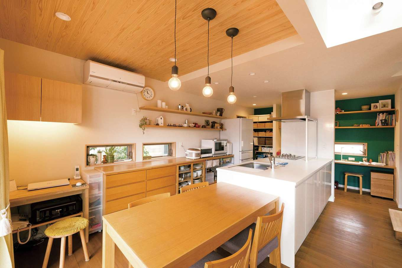 フジモクの家(富士木材)【デザイン住宅、自然素材、インテリア】夫妻のセンスと暮らしぶりが伝わってくるDK。天井の杉板とワークスペースのクロスが、空間の役割を穏やかに分割する。左手の作業机は造作で、来客時にはダイニングテーブルにつけて使えるよう高さがそろえられている