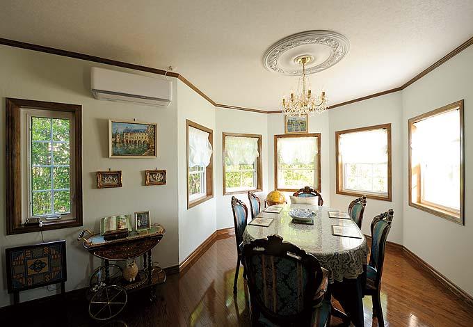 八角形の塔屋の1 階にはダイニングを配した。どの席からも庭の緑が楽しめ、伸びていく視線が広さを感じさせる。天井の照明取り付け部にはメダリオン貼り。食卓を優雅に彩る