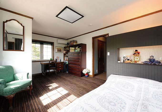 書庫を備えた主寝室。抑えたトーンのカーペット、造作のベッドヘッドがくつろぎを運ぶ