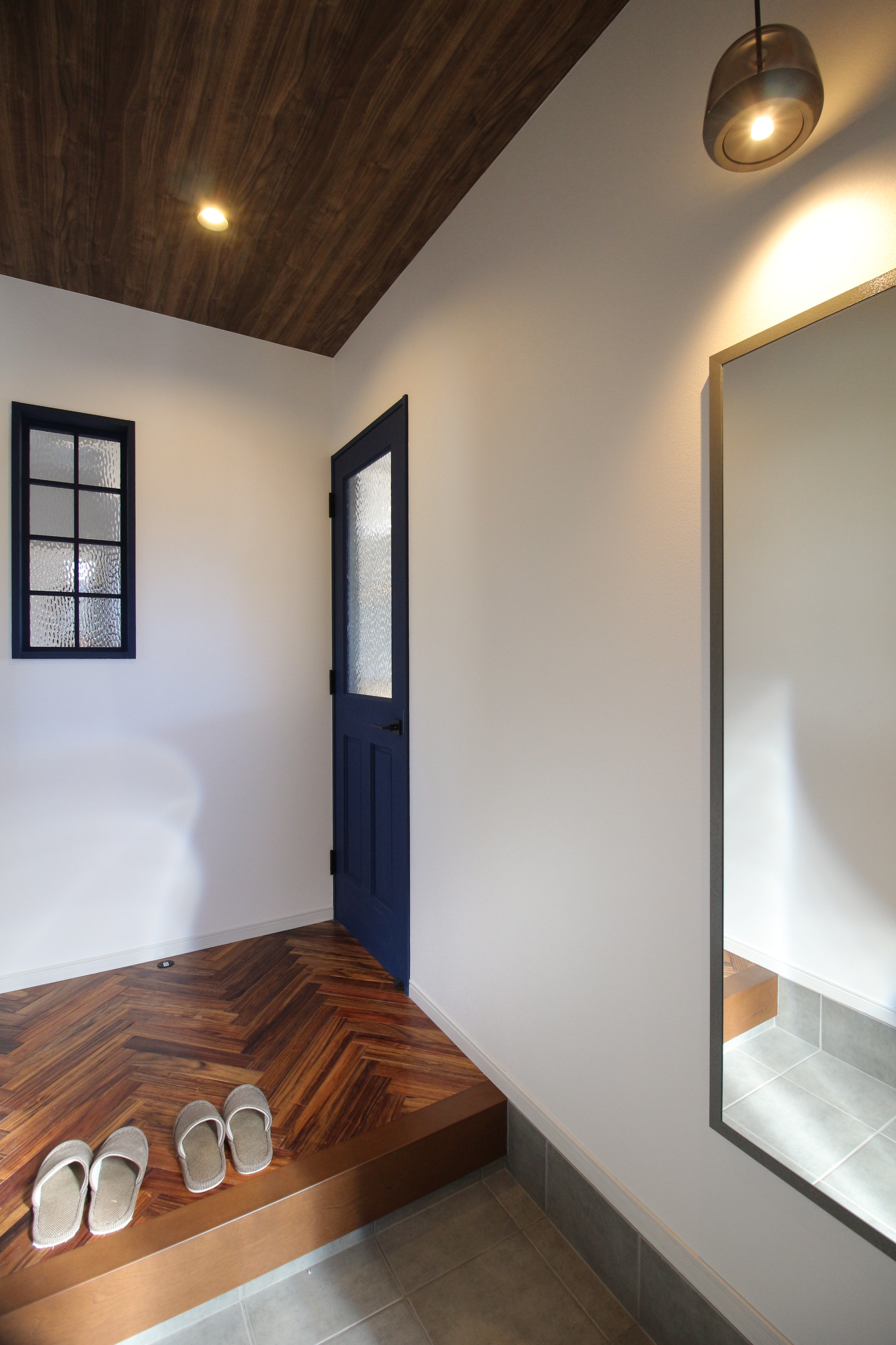 お客さまを迎える玄関は無垢材を使ったヘリンボーン床が映える