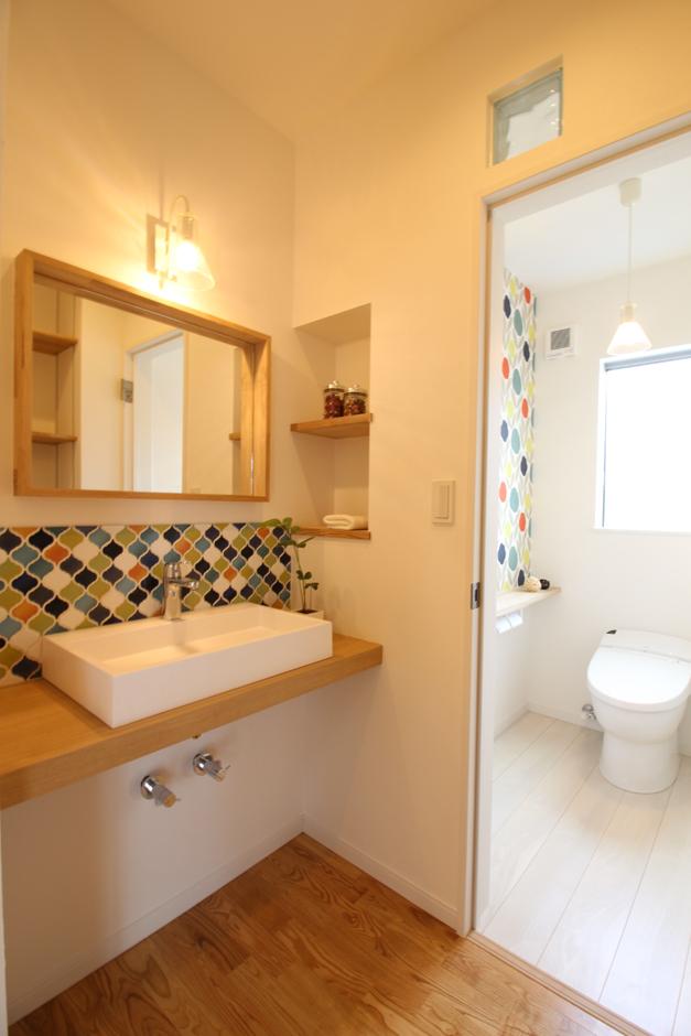 手洗い場のタイルに合わせトイレの壁面も同色系でコーディネート