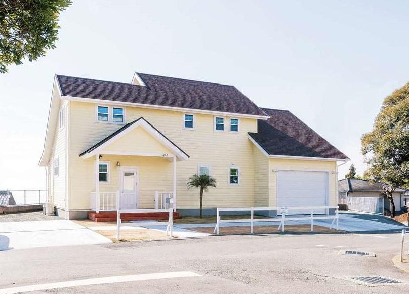富士ホームズデザイン【デザイン住宅、趣味、建築家】軽やかな色合いに仕上げたレッドシダーの壁が西海岸の風を感じさせる。玄関ドアや照明は輸入物。ご主人お手製の白い柵や同社がプレゼントしたヤシの木も雰囲気にピッタリ!
