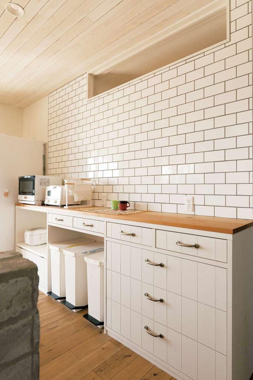 富士ホームズデザイン【デザイン住宅、趣味、建築家】タイル張りのキッチンは色味をあわせてカウンターを用意。収納量はパントリーに任せ、キッチン回りはすっきり&便利に。ゴミ箱の工夫など上総さんの女性目線がキラリ