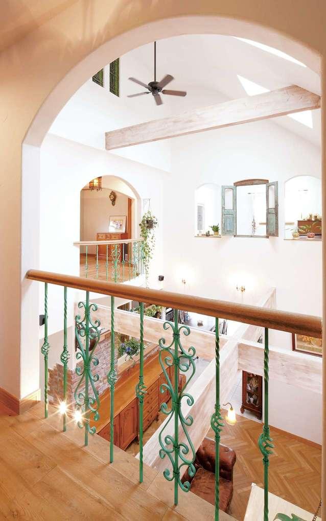 富士ホームズデザイン【デザイン住宅、輸入住宅、高級住宅】2階から見た吹き抜け。グリーンで塗装したアイアンの手すり、向かい側にある寝室の扉つき小窓もいい感じ