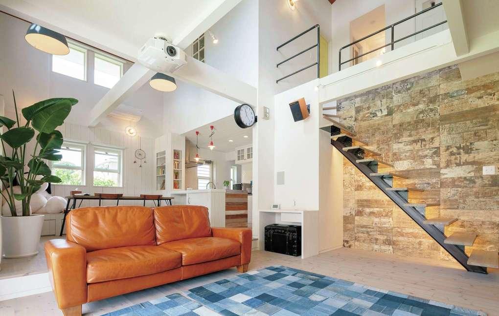 富士ホームズデザイン【デザイン住宅、趣味、間取り】リビングとダイニングは床の高さを変えてゾーニング。どちらも吹き抜けの開放的な空間だ。アイアンで製作したオリジナル階段は、タイル壁と間接照明でセンスアップ