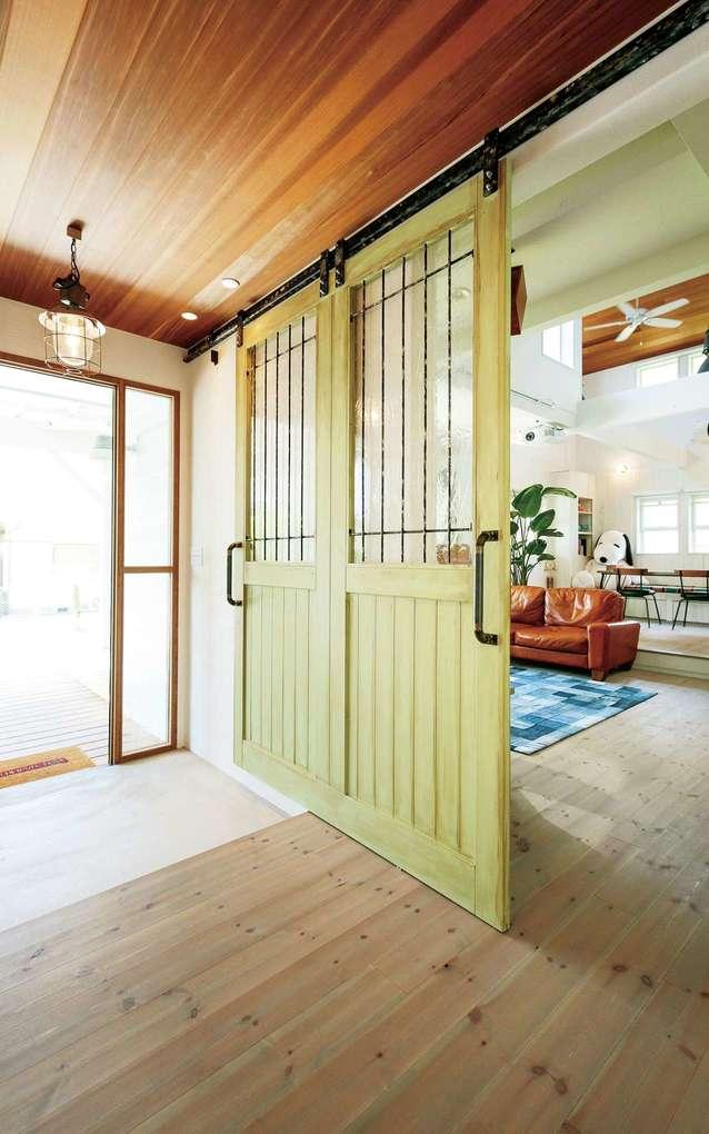 富士ホームズデザイン【デザイン住宅、趣味、間取り】玄関とリビングを仕切るオリジナルドア。2枚に見えるが実は1枚という技ありのデザイン。上から吊ってあるので重くてもスムーズに開け閉めできる