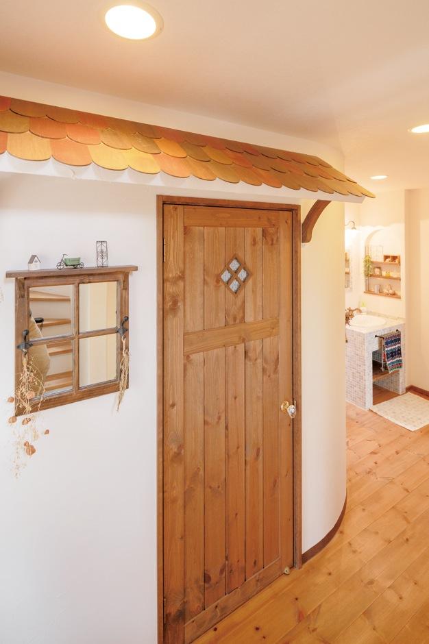 人気のオリジナルデザインを2階にも。寝室のドアは玄関のイメージで窓と屋根をつけ、壁もアールにして建物の外観らしく。ご夫婦ともお気に入りの場所だそう