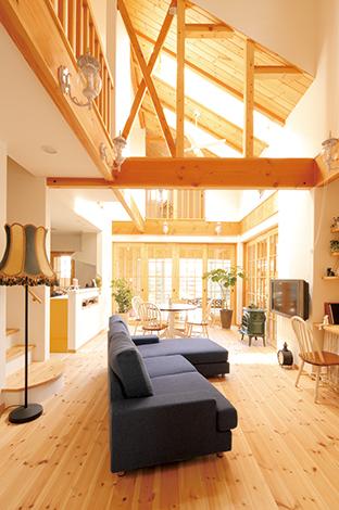 パイン無垢材を床と勾配天井に使い、大きなトップ ライトを2つ。梁の上は壁を作らず、あえてそのま まにしたことで空間に広がりが生まれ、リゾート感 がアップ。最初は木を濃色に塗る予定だったが、無垢材の質感をそのまま活かしてナチュラルな雰囲 気に仕上げた