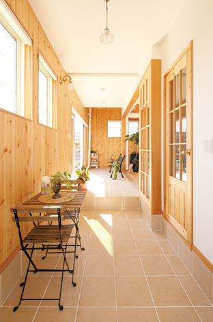 玄関からホールまでタイルの床を張り巡らせ、リビングを囲むようにL字型に配置されたインナーテラス。リビングとの間にはフルオープンにできるガラス戸を設け、夏は開け放って風を通 し、冬は閉めてトップライトから差す日光で部屋を暖めることができる。パインの板壁がリゾートハウスの雰囲気にぴったり