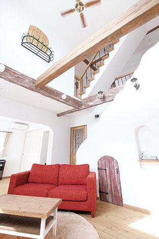 富士ホームズデザイン【デザイン住宅、輸入住宅、自然素材】リビングから見た階段のアールと手すりのアイアンがいい感じ。階 段下収納のドアも手作り
