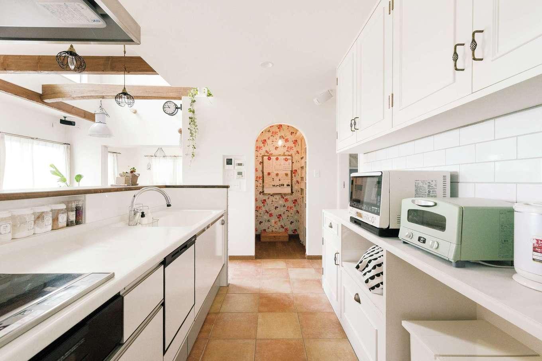 富士ホームズデザイン【デザイン住宅、趣味、自然素材】手元が見えないように工夫したキッチン。オリジナル収納は扉のデザインや取っ手まで吟味して造作した。正面奥はパントリー。花柄クロスとアールの入り口にも注目