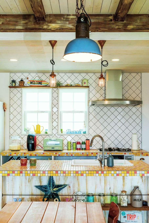 富士ホームズデザイン【デザイン住宅、建築家、インテリア】モザイクタイル貼りのキッチン、斜めに貼った壁のタイル、アンティーク照明、それぞれの個性が絶妙にマッチしたダイニング。「キッチンのモザイクタイルは私の好きな黄色をベースに、設計の上総専務がアクセントカラーをほどよくプラスしてくれたおかげで、こんなにオシャレに仕上がりました」と奥さまもにっこり