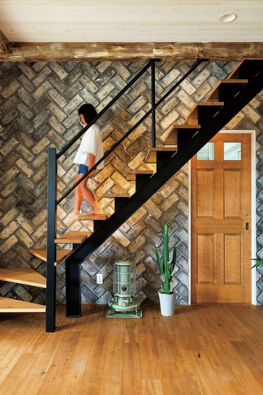 富士ホームズデザイン【デザイン住宅、建築家、インテリア】アンティークレンガのアクセントウォールがLDK全体をワンランク上の空間に引き立てている。木の階段やアイアンの手すりとの相性も抜群