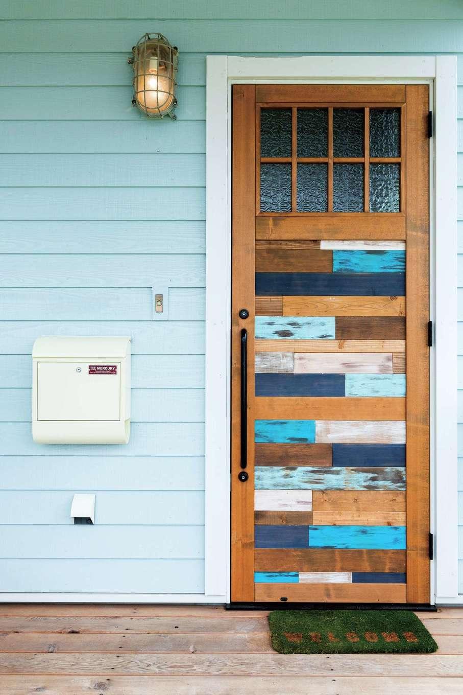 富士ホームズデザイン【デザイン住宅、建築家、インテリア】『富士ホームズデザイン』オリジナルの玄関ドア。表面はブルーを効かせて外観のアクセントに。裏面は茶色を基調にデザイン。照明はアンティークの船舶用ライト