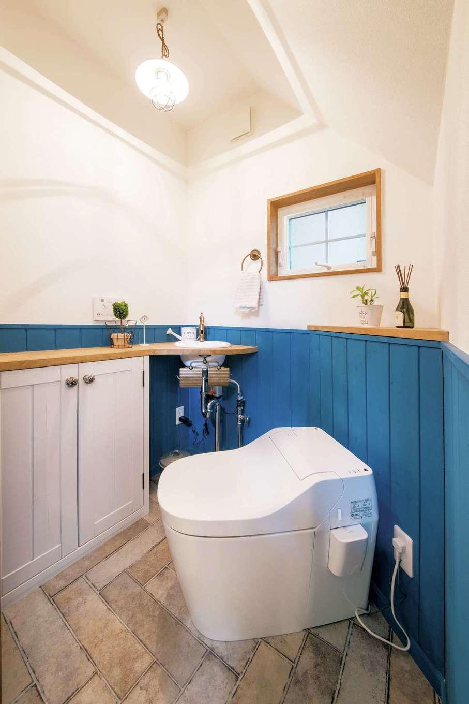 ブルーに塗装した高めの腰板がかわいい。トイレを斜めにした配置もユニーク