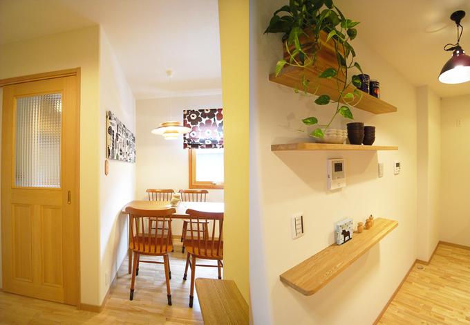 造作の木製ドアや木の棚が白い壁にぽっかりと浮かんだナチュラルな空間の中に、ファブリックや植物の濃い目のトーンを華やかに飾るインテリア