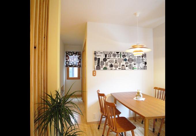 マリメッコのファブリックの持つ大胆な図柄と配色が木製家具とマッチするダイニングスペース