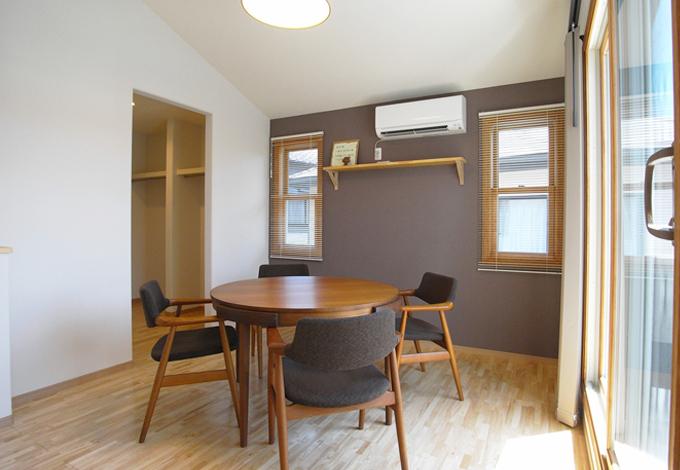 ベッドの位置にテーブルがあるが主寝室である。一面だけ色を変えた壁に木製の窓がシンメトリー配された寛ぎの空間。奥に見える入口はウォークインクローゼット