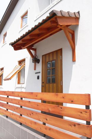 壁に埋め込まれた玄関ポーチを支える無垢材で組まれたヤグラ。和に通じる北欧スタイル
