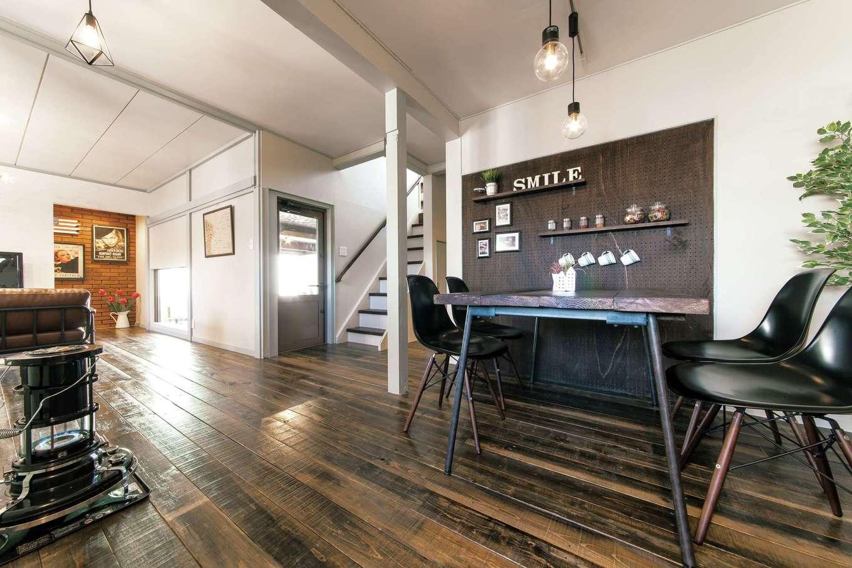 Sanki Haus(サンキハウス)静岡三基|LDKの床はダークカラーに塗装したヴィンテージウッドで統一。足場板とアイアンで造作したダイニングテーブルなど、インテリアの提案も魅力的。残した柱の傷やほぞ痕は、本物のヴィンテージ