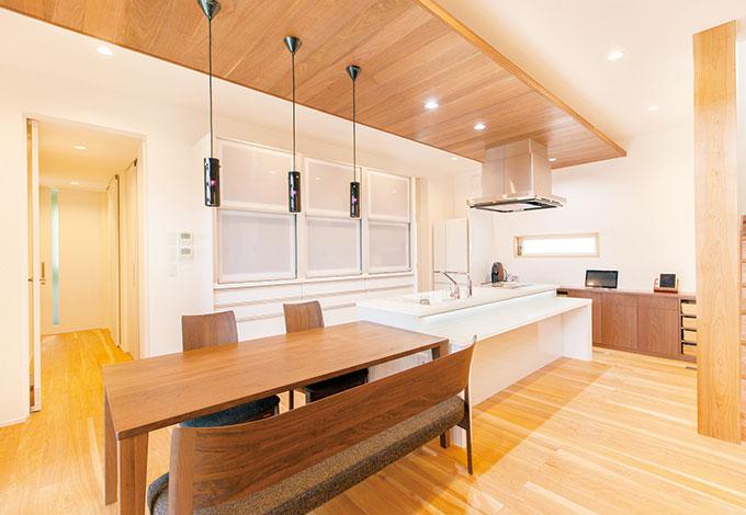 ひらおか建築【デザイン住宅、省エネ、建築家】ダイニングキッチンの天井の一部にウォルナットを使用。造作のカウンター収納や家具も同 一素材でそろえ、モダンなLDKに落ち着きとあたたかみを添えた。背後に回遊性のある収納と 水回りが続き、家事の負担を軽くしている