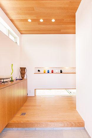 ひらおか建築【デザイン住宅、省エネ、建築家】玄関は床、天井、下駄箱をブラックチェリーで統 一。横長の窓とニッチも、モダンな印象に一役