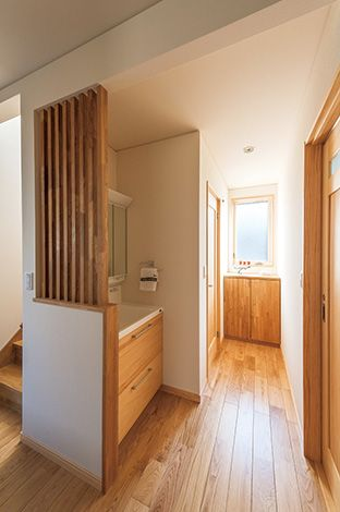 廊下の洗面台は、 木のスリットが部 屋のアクセントに なり、さりげなく目隠 しの役目も果たし ている