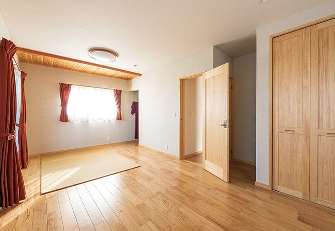 いずれ親御さんとの同居を想定して、分割可能な作り にした寝室。天井の両端に施されたスギ板が、部屋に 表情を与えている
