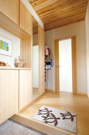 玄関ホールの収納棚も無垢の木で造作。洋服をハンガーに掛けられるスペースも便利!