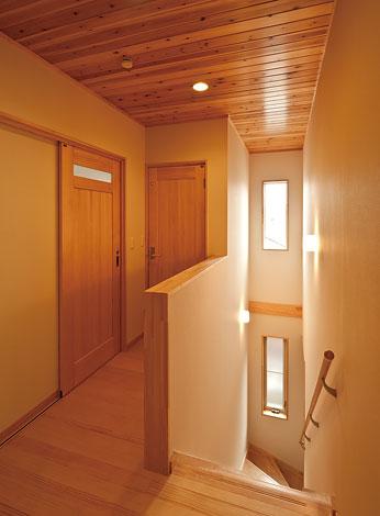 2つの窓から朝日が差し込む吹き抜け階段。リビングを出るとすぐにバスルーム、トイレにいくことができる