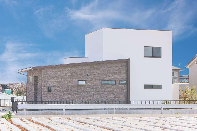 ARRCH アーチ【デザイン住宅、収納力、二世帯住宅】1階と2階のボリューム差をいかしたインパクトのある外観。平屋部分はタイル貼り、白い2階建て部分は漆喰塗で仕上げ、素材のコントラストが個性を奏でている