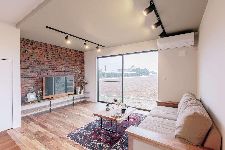 ARRCH アーチ【デザイン住宅、収納力、二世帯住宅】リビングとダイニングは天井の高さに変化をつけることで、空間の広がりにメリハリを演出。TV背面のアンティークレンガ貼りの壁はご主人のこだわり。アカシアの無垢ともベストマッチ