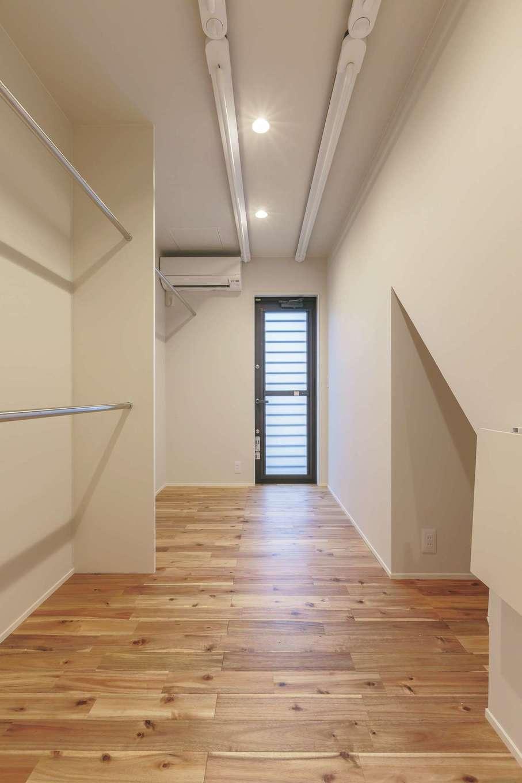 ARRCH アーチ【デザイン住宅、収納力、二世帯住宅】洗面脱衣室の向かいにファミリークローゼットを配し、天井に室内干しを設置。乾いたらハンガーに移動するだけで済み、洗濯の動線を画期的に短縮。外干し用の勝手口もある