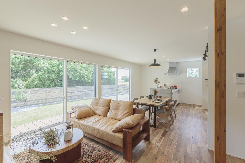 ARRCH アーチ【デザイン住宅、間取り、建築家】南面の広い窓から緑の庭の風景を採り込み、爽やかで開放感あふれるLDKが実現。無垢の床は足触りが良く温かみがあって、素足の生活を年中楽しめる。キッチンの奥は水回りに通じ、玄関・LDK・水回りをぐるりと回れる回遊動線を確保したことで、家事が格段と便利に。仕事と家事と育児で忙しい奥さまの家事の負担を軽減し、時間にゆとりをもたらしてくれる