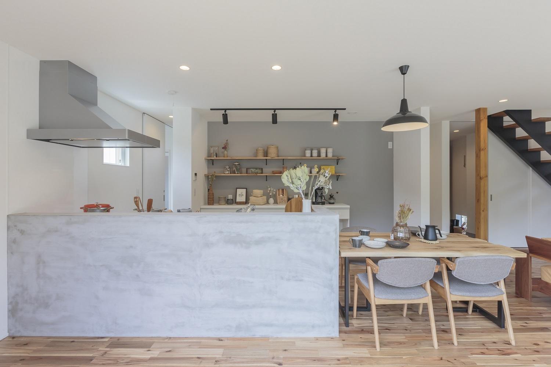 ARRCH アーチ【デザイン住宅、間取り、建築家】腰壁をモルタルで仕上げたオシャレなキッチンスペース。キッチンに立つと室内全体と庭が見渡せて、いつもお子さまの様子を見守っていられるから安心