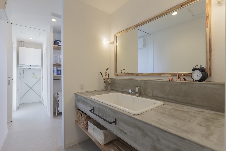 ARRCH アーチ【デザイン住宅、間取り、建築家】モルタル仕上げのオリジナル洗面台。鏡もカウンターもワイドサイズにして、朝の仕度が重なっても困らないようにした。奥さまもゆっくりとスキンケアやメイクを楽しめそう